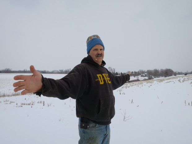 Farmer Rob Fulper stretches his arms out to show the path of a pipeline underneath his corn field in West Amwell, NJ.