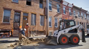 A Philadelphia Gas Works crew back fills part of Van Pelt Street after replacing aging gas lines in North Philadelphia. (Lindsay Lazarski/WHYY)