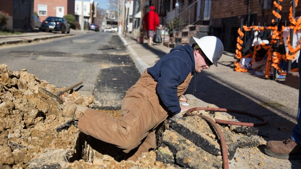 Michael Groves, PGW Senior Pipe Mechanic climbs out of a hole on Van Pelt Street after inspecting a new main gas line in North Philadelphia.