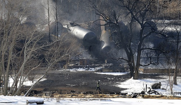 This Feb. 17, 2015 file photo shows a crew member walking near the scene of a train derailment near Mount Carbon, W.Va.