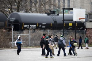 In this photo taken April 9, 2015, children play in view of train tank cars with placards indicating petroleum crude oil standing idle on the tracks, in Philadelphia. Rail tank cars that are used to transport most crude oil and many other flammable liquids will have to be built to stronger standards to reduce the risk of catastrophic train crash and fire under a series of new rules unveiled Friday by U.S. and Canadian transportation officials.