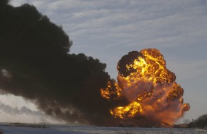 In this Dec. 30, 2013 file photo, a fireball goes up at the site of an oil train derailment in Casselton, N.D.  On Tuesday, March 31, 2015, Bryan Thompson, of Fargo, N.D., the engineer of the oil tanker train involved in the derailment, filed a complaint against BNSF Railway, accusing the railroad of negligence. Thompson says BNSF failed to properly inspect and maintain its equipment and failed to warn him of the dangers of hauling explosive oil tank railcars