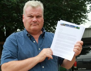 Scott Cannon holding a letter of acceptance to the DEP's pipeline task force.