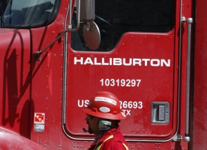 An unidentified worker passes a truck owned by Halliburton at a remote site for natural-gas in Colorado.