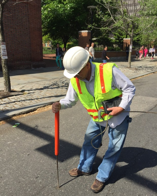 Bob Ackley uses a bang bar to drill a small hole in the street to check for gas leaks.