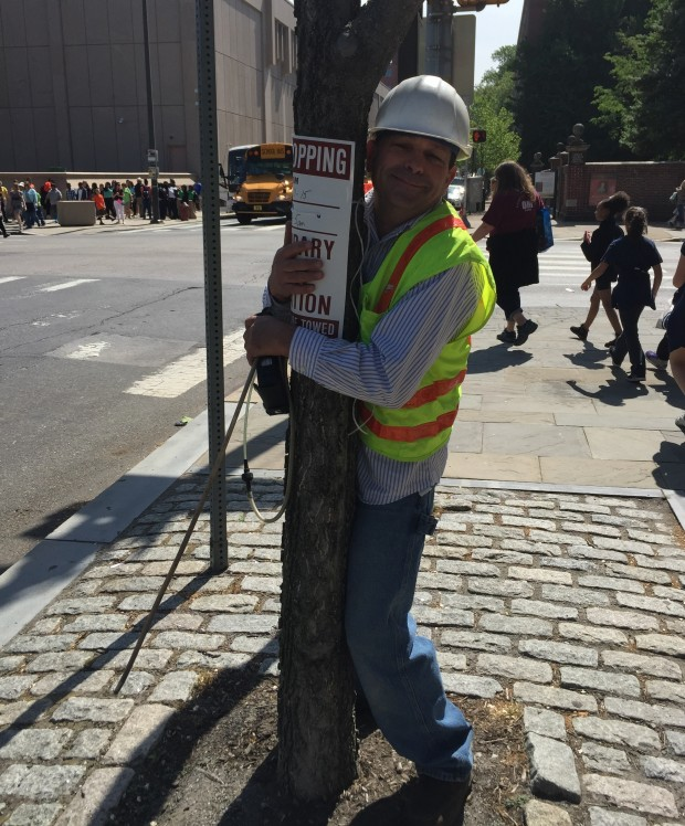 Gas safety consultant Bob Ackley hugs a dead tree across the street from the Constitution Center in Philadelphia.