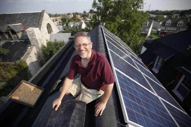 Tim Johnson poses for a portrait with solar panels on his roof  in Philadelphia, September, 2011.