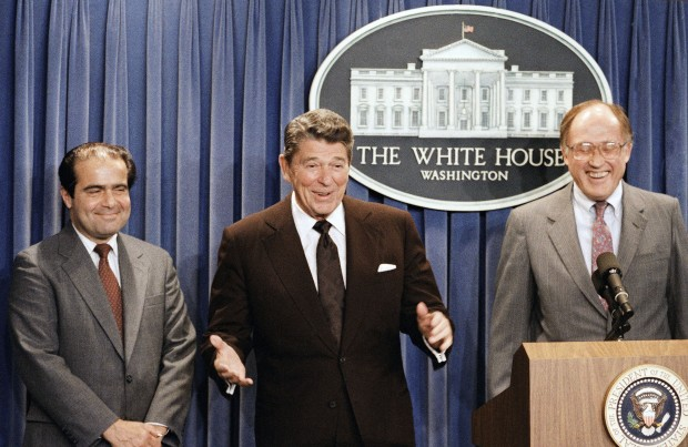 In this June 17, 1986 file photo, President Ronald Reagan speaks at a news briefing at the White House in Washington, where he announced the nomination of Antonin Scalia, left, to the Supreme Court as a result of Chief Justice Warren E. Burger's resignation. William Rehnquist is at right. On Saturday, Feb. 13, 2016, the U.S. Marshals Service confirmed that Justice Scalia has died at the age of 79.