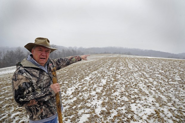 Gene Meyers points toward one of Apex Energy's proposed well sites from a hill by his home near Dutch Hollow Road in the Penn Township.