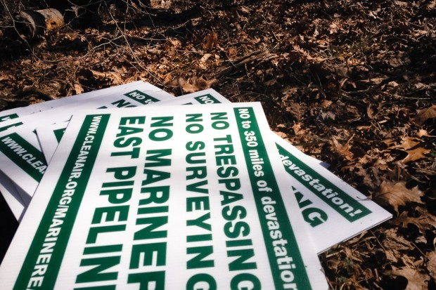 A stack of protest posters opposing Sunoco's Mariner East 2 lie in a wooded area of the Gerhart property.