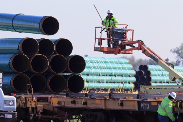 Workers unload pipes at a staging area in Worthing, S.D., for the proposed 1,130-mile Dakota Access Pipeline that would stretch from the Bakken oil fields in North Dakota through South Dakota and Iowa to a hub in Illinois.