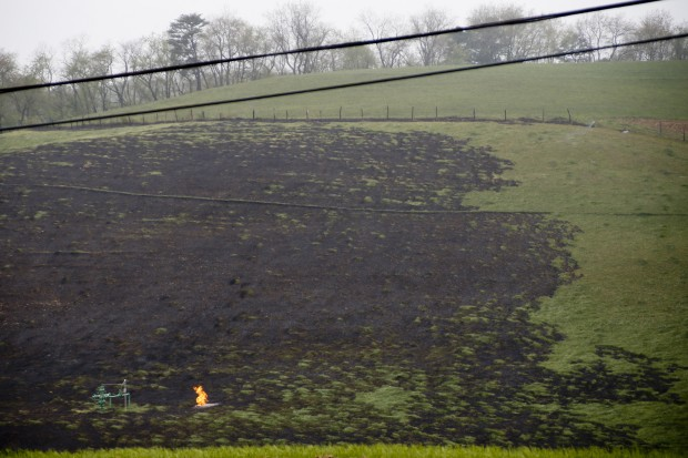 A flame flickers near a protrusion of pipes at the area where a natural gas explosion at a pipeline complex burned one person and damaged houses on Friday, April 29, 2016, in Salem Township, Pa. The explosion caused flames to shoot above nearby treetops in the largely rural area, about 30 miles east of Pittsburgh, and prompted authorities to evacuate businesses nearby.