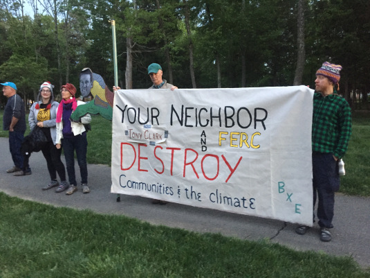 Pipeline opponents and climate activists protest outside the home of FERC commissioner Clark. The activists say FERC is a captured agency that rubber stamps pipeline projects.