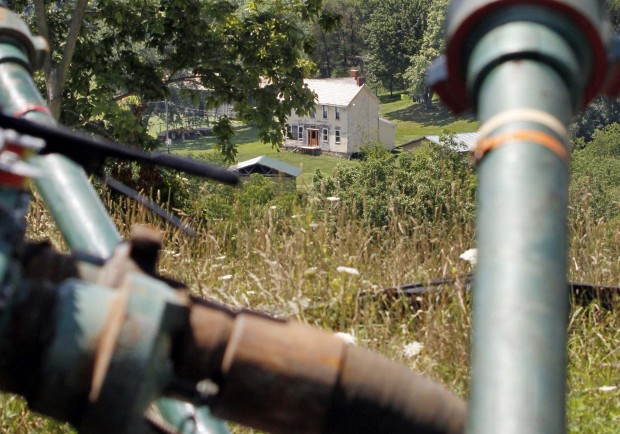 FILE PHOTO: This 2011 file photo shows a farmhouse in the background framed by pipes connecting pumps where the hydraulic fracturing process in the Marcellus Shale layer to release natural gas was underway at a site in Claysville, Pa.