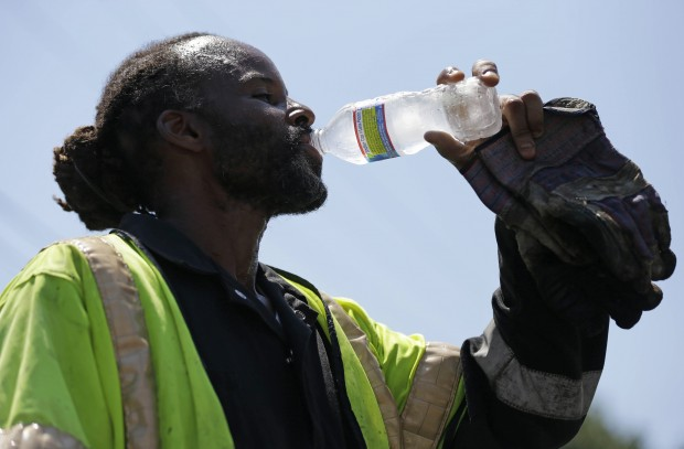 A paving crew member takes a drink of water during a record-breaking heat wave, July 6, 2012, in Philadelphia.  is among Pennsylvania cities facing an increase in high temperatures and humidity caused by climate change, report warns.
