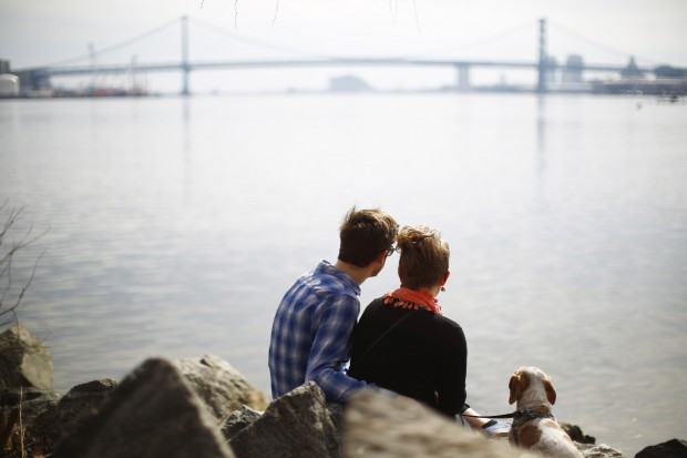 Brian Clores, left, Carissa Arty and their dog Elvis sit on the banks of the Delaware River in view of the Benjamin Franklin Bridge on a warm winter afternoon, Wednesday, March 11, 2015, at Penn Treaty Park in Philadelphia.
