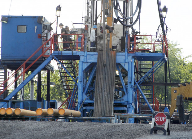 A crew works on a drilling rig in Zelienople, Pa. file photo