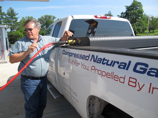 A man fills up a pickup truck that runs on compressed natural gas (CNG) at a gas station in Towanda, Bradford County.