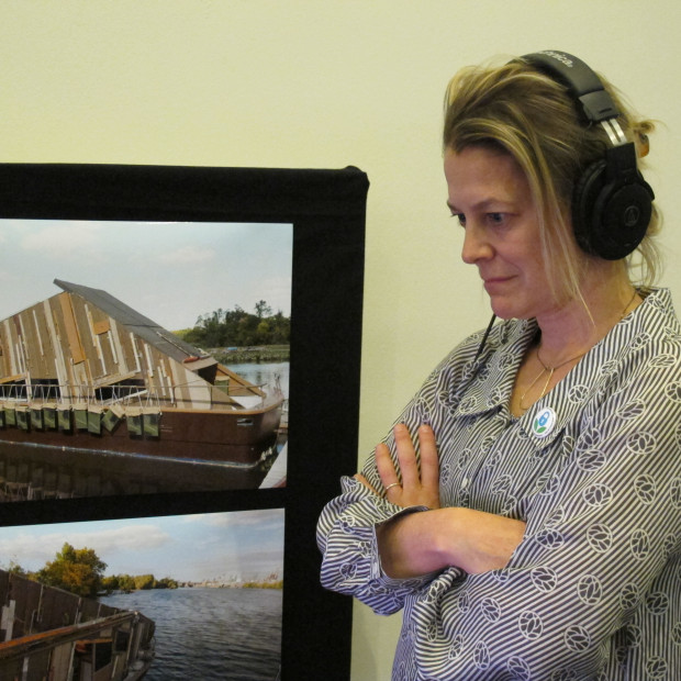 Bethany Wiggin, who runs Penn's program in environmental humanities listens to audio from the Date-um exhibit, which focuses on water quality in the lower Schuylkill river.