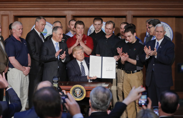 President Donald Trump, accompanied by Environmental Protection Agency (EPA) Administrator Scott Pruitt, third from left, and Vice President Mike Pence, right, is applauded as he hold up the signed Energy Independence Executive Order, Tuesday, March 28, 2017, at EPA headquarters in Washington.