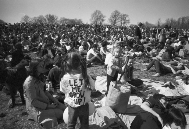 "Part of crowd observing Earth Day, including, youngster wearing ""Let Me Grow Up:"" sign on back relaxes on hilltop in Philadelphia's Fairmount Park Wednesday, April 23, 1970. Crowd made up mostly of young people, was estimated at more than 20,000 persons."