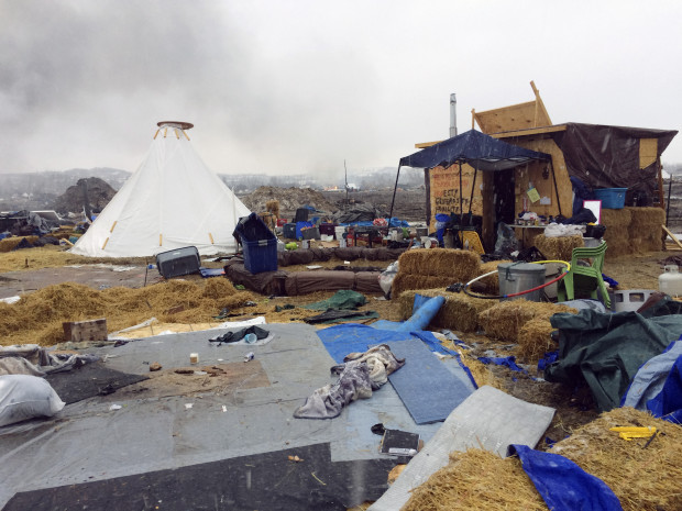 Feb. 22, 2017: Refuse remained in the Dakota Access pipeline opponents' main protest camp as a fire burns in the background in southern North Dakota near Cannon Ball, N.D.