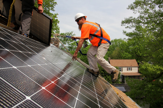 Dennis Hajnik installs solar panels on a roof in Bryn Mawr, Delaware County.