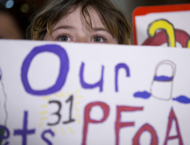 In this June 15, 2016 file photo, a girl holds a sign during a news conference at the state Capitol in Albany, N.Y., calling for hearings on the state's handling of PFOA contamination in drinking water in Hoosick Falls. New York environmental regulators are looking statewide for potential sites of groundwater contamination from a cancer-causing chemical previously used to make Teflon and other products. The Department of Environmental Conservation sent formal surveys last week to more than 150 facilities that may have used PFOA. Surveys were also sent to scores of fire departments, airports and other facilities that may have used the related chemical PFOS in firefighting foam.