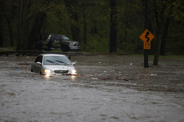 A man waves for a tow truck after getting swamped trying to cross a flooded section of the Cobbs Creek Parkway, Wednesday, April 30, 2014, in Philadelphia. Cobbs Creek and Darby Creek merge in the Eastwick section of Philadelphia where flooding is expected to get worse due to rising sea levels.