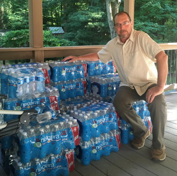 Benjamin Eckert, a resident of Chester County's West Whiteland Township, with some 30 cases of bottled water that Sunoco had delivered to his house after water from his well turned cloudy. Sunoco is drilling nearby for the planned Mariner East 2 pipeline, and hit the aquifer from which Eckert and his neighbors draw their water.