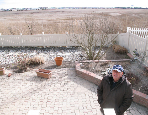 This Feb. 16, 2017 photo shows Marty Mozzo in his back yard in Ocean City N.J. on the edge of a back bay wetlands. When he and his wife were considering buying the house, they looked at a small trickle of water in the distance and wondered if the property would flood, deciding the water was too far away to pose a danger. Within weeks, their hou8se was surrounded by flood waters.