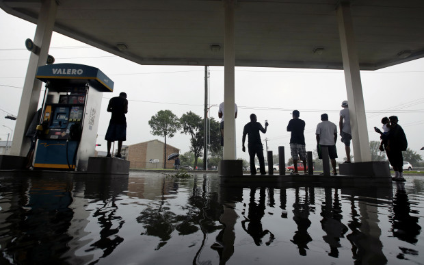 People watch heavy rain from the relative safety of a flooded gas station caused by  Tropical Storm Harvey on Sunday, Aug. 27, 2017, in Houston, Texas.
