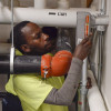 Richard Tumushime, an electrician with Pittsburgh-based Energy Independent Solutions, works with a crew to put the finishing touches on wiring a solar panel system at the new Forest Hills Municipal Building.