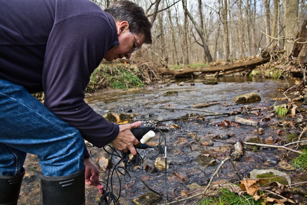 John Jackson, a senior research scientist at the Stroud Water Research Center, measuring conductivity at the White Clay Creek at the center.