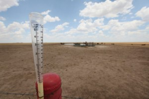 An empty rain gauge is strapped to a fence post on the edge of a pasture this summer near Canadian, Texas