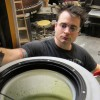UT Research Engineer Robert Pearsal looks into a vat of algae.