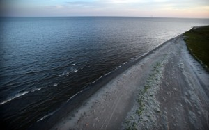 The sun sets waves wash up from the Gulf of Mexico onto the beach April 13, 2011 in Isla Grand Terre, Louisiana. T
