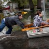 A man pushes a woman and a dog in a boat a boat after their neighborhood experienced flooding due to Hurricane Sandy, on October 30, 2012, in Little Ferry, New Jersey.