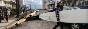 Martina Melendez salvages a surfboard from a flooded bungalow following Superstorm Sandy at Rockaway Beach on November 3, 2012 in the Queens borough of New York City.