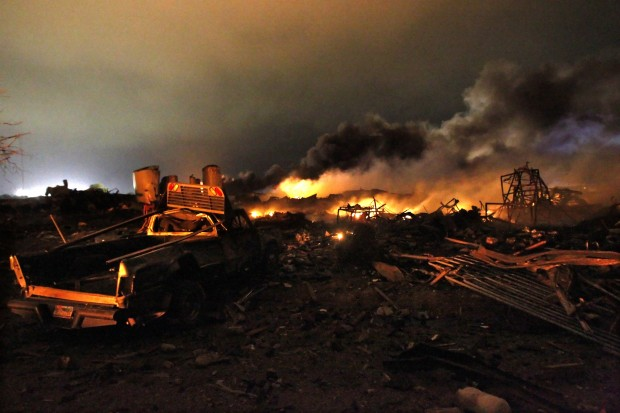 A vehicle is seen near the remains of a fertilizer plant burning after the explosion.