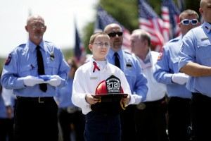 A helmet is carried in remembrance of a firefighter from the Abbott Volunteer Fire Department killed in the fertilizer plant explosion in West, Texas last year.
