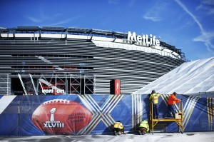 Workers prepare a fence with Super Bowl ads at the Metlife Stadium in East Rutherford, New Jersey, January 28, 2014. The stadium's solar panels are visible on the roof.