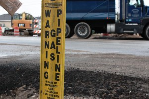 Temporary sign marks where gas pipeline is buried along road in Harris County