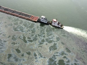 A barge loaded with marine fuel oil sits partially submerged in the Houston Ship Channel in this U.S. Coast Guard picture taken March 22, 2014. The barge leaked oil into the Houston Ship Channel after colliding with another ship near Texas City on Saturday and emergency responders laid down floating barriers to contain the spill, U.S. Coast Guard officials said. The barge, which was being towed by the motor vessel Miss Susan, contained 168,000 gallons (636,000 liters) of fuel oil in the tank that was breached in a collision with a bulk carrier, the Summer Wind, said a Coast Guard spokeswoman.