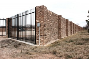 Gated gas: brick wall surrounds gas well site near neighborhoods on Fort Worth's east side