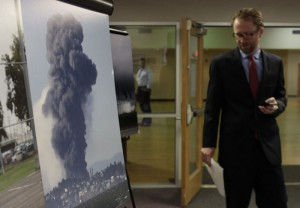 Luke Metzger, Environment Texas, who testified at EPA hearing, passing by a photo of a refinery explosion in California.