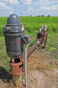 A motorized pump draws aquifer water up to the surface to irrigate the rice crop in the background.